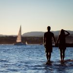 Couple at ocean with sailboat in background
